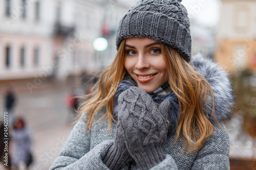 Obraz Portrait of a wonderful young woman with beautiful blue eyes with natural make-up in a sweet smile in a knitted hat in knitted mittens in a stylish coat on the background of city streets. Happy girl. - fototapety do salonu