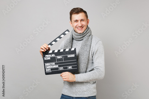Fototapeta Smiling young man in gray sweater, scarf holding classic black film making clapperboard isolated on grey background