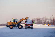 Snow Cleaning In Airport. Excavator Loads Snow Into Dump Truck