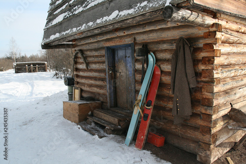 Siberian hunting hut in winter with skis at the entrance