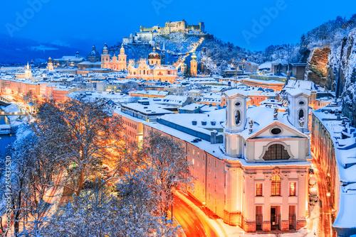 Fototapeta premium Salzburg, Austria: Zimowy widok na historyczne miasto Salzburg ze słynnym Festung Hohensalzburg i rzeką Salzach oświetlone w pięknym zmierzchu podczas malowniczych świąt Bożego Narodzenia w zimowym
