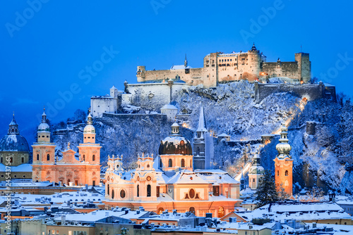 Fototapeta premium Salzburg, Austria: Zimowy widok na zabytkowe miasto Salzburg ze słynnym Festung Hohensalzburg i rzeką Salzach oświetloną o pięknym zmierzchu podczas malowniczych świąt Bożego Narodzenia w zimę