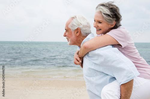 Valokuva  Senior man giving smiling woman piggyback ride on beach vacation