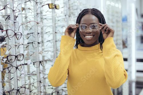 Fotografía  Young pretty african woman choosing prescription glasses frames in Optician's shop