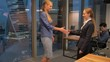 Two Happy young businesswomen shaking hands inside of modern business coworking office. Super slow motion middle shot