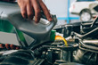 Auto mechanic working in garage during the maintenance of engine. Mechanician pouring fresh oil during Repair of a car in auto service garage