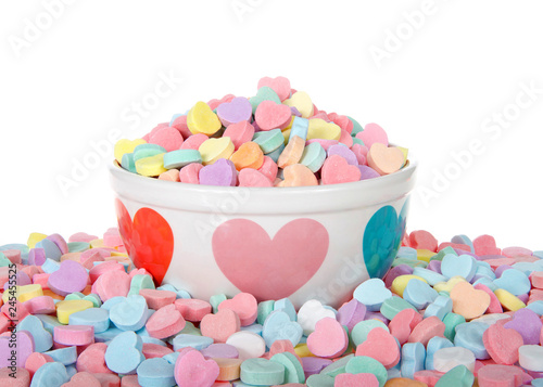 Fotografie, Obraz  Bowl with hearts holding pile of candy hearts surrounded by pile of more candy isolated on white background