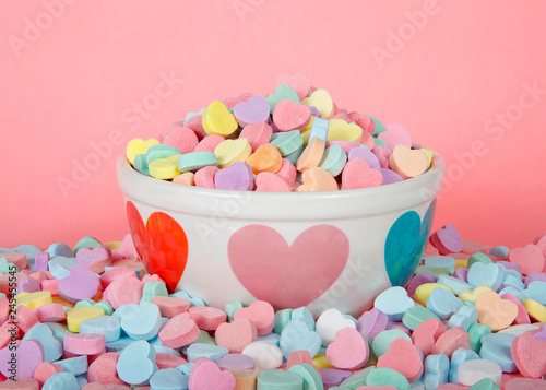 Bowl with hearts holding pile of candy hearts surrounded by pile of more candy  on pink background. Traditional Valentine's Day candy.