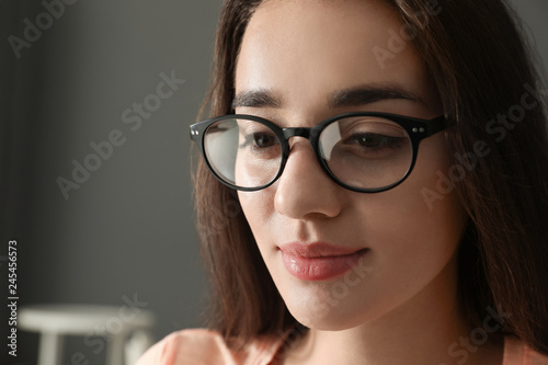 Beautiful young woman wearing glasses on blurred background. Ophthalmologist service