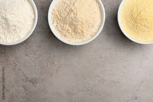 Bowls with different types of flour on grey background, top view. Space for text