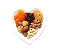 Heart Shaped Plate With Different Dried Fruits And Nuts On White Background, Top View