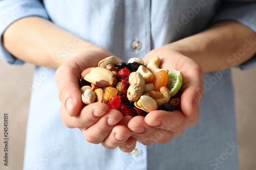 Young woman holding handful of different dried fruits and nuts, closeup