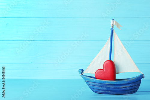 Fotografia  Toy boat with red heart on table against color background