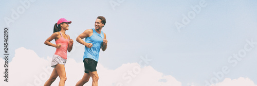 Healthy people fit active lifestyle couple running on sky background panoramic banner. Happy friends exercising together -training buddy.