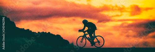Road bike triathlon race cyclist on racing bike biking competition at sunset background sky banner panorama.