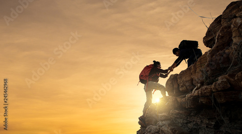 Fotografía  Asia couple hiking help each other silhouette in mountains with sunlight