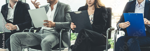 Photo Businesswomen and businessmen holding resume CV folder while waiting on chairs in office for job interview