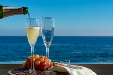 Waiter Pouring Champagne, Prosecco Or Cava In Two Glasses On Outside Terrace With Sea View