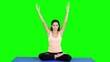 Attractive young woman doing yoga and meditating while sitting on yoga mat in the studio. Shot in 4k resolution with green screen