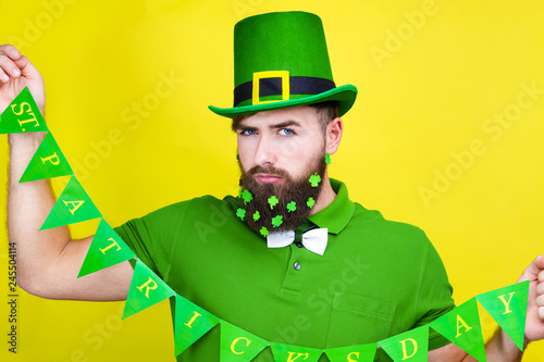 Happy young adult man male in green shirt, green leprechaun hat and tie bow with Wallpaper Mural