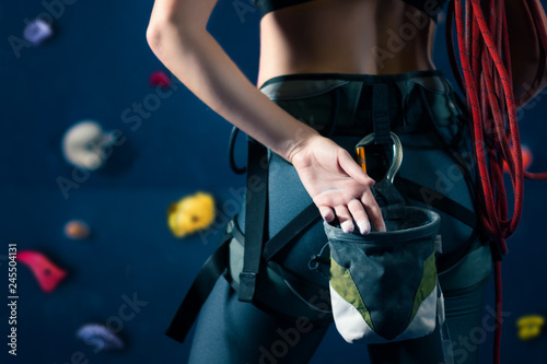 Photo Successful strong self confident sport woman female alpinist climber staying opposite wall before training bouldering on climbing wall
