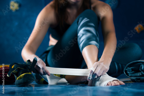 Successful strong self confident sport woman female alpinist climber treats injuries wounds after training bouldering on climbing wall Canvas Print