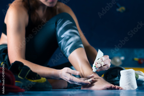 Photo Successful strong self confident sport woman female alpinist climber treats injuries wounds after training bouldering on climbing wall