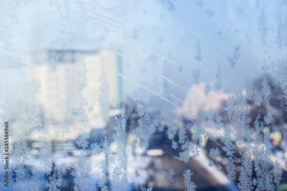 shiny ice patterns on a bright window behind which the urban landscape is blurred