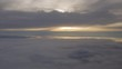 Aerial view floating towards the sun setting between the clouds high in the sky