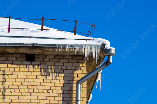 Fotografia, Obraz  The drain pipe and icicles on the roof edge of the building in the spring