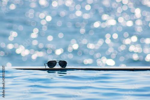 Cuadros en Lienzo Sunglasses near the edge of a swimming pool