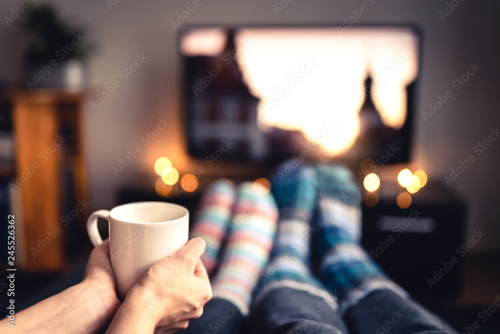 Fototapeta Couple drinking tea, hot chocolate, eggnog or mulled wine and watching tv in warm cozy woolen socks in winter. Woman holding cup of morning coffee in home living room. Sick people with flu or fever.