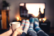 Leinwandbild Motiv Couple drinking tea, hot chocolate, eggnog or mulled wine and watching tv in warm cozy woolen socks in winter. Woman holding cup of morning coffee in home living room. Sick people with flu or fever.