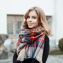 Portrait Of An Attractive Woman With Blond Hair With A Wonderful Smile In A Black Stylish Coat With A Woolen Checkered Warm Scarf On The Background Of A Gray Historic Building. Lovely Girl Smiling