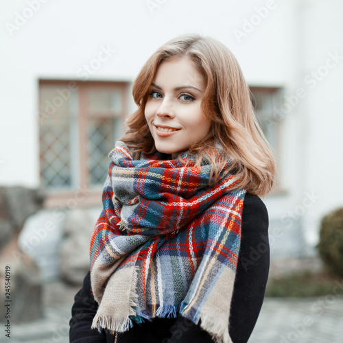 Valokuvatapetti Portrait of an attractive woman with blond hair with a wonderful smile in a black stylish coat with a woolen checkered warm scarf on the background of a gray historic building