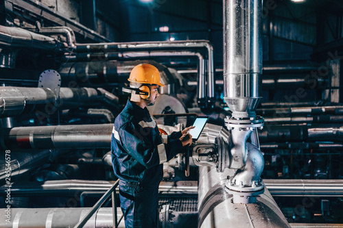 Portrait of young Caucasian man dressed in work wear using tablet while standing in heating plant Wallpaper Mural