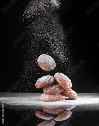 печенье  с сахарной пудрой на черном фоне