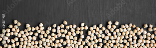 Fotografie, Obraz  Dried chickpeas on a black background, top view. Flat lay.