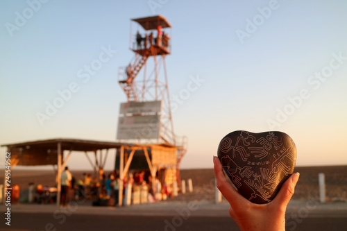 Poster Zuid-Amerika land Woman's hand holding a souvenir of Nazca lines carved heart shaped stone against blurry observation tower of Nazca, Ica region, Peru, South America