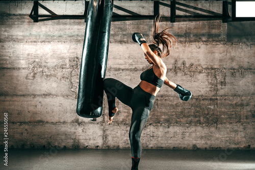 Photo Dedicated strong brunette with ponytail, in sportswear, bare foot and with boxing gloves kicking sack in gym