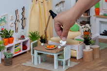 A Cheerful Bright Room In A Doll House Furnished With Miniature Furniture, A Person Serving Tea From A Teapot For A Play