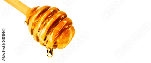 Honey dripping from honey dipper isolated on white background Tableau sur Toile