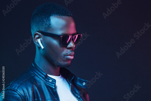 La pose en embrasure Magasin de musique Handsome African American man wearing wireless earphones and leather jacket