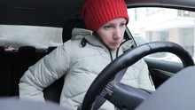Woman In Winter Clothes And Orange Knitted Hat Fasten Seat Belt In A Car, Ready To Drive