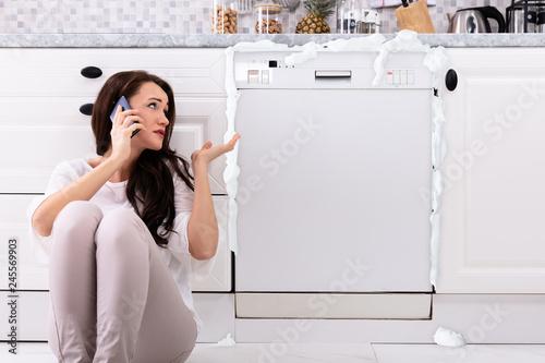 Sad Woman Sitting Next To Damaged Dishwasher Calling Technician Fototapet