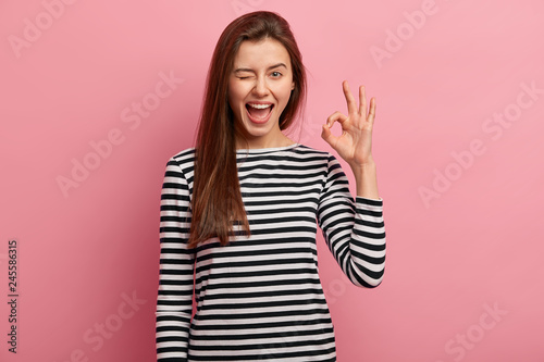 Leinwand Poster Photo of cheerful young woman blinks eye, makes okay gesture, demonstrates her agreement, feels happy, wears black and white striped jumper, isolated over pink background
