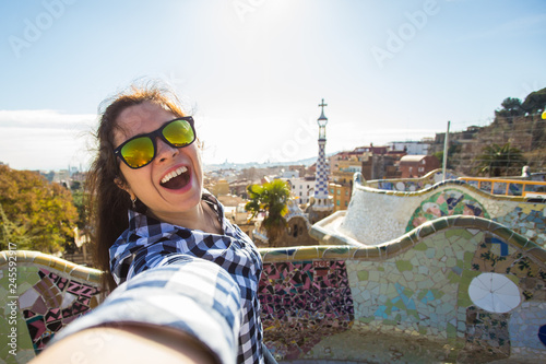 Fotografie, Tablou  Travel and holidays concept - Young happy woman making selfie portrait with smartphone in Park Guell, Barcelona, Spain