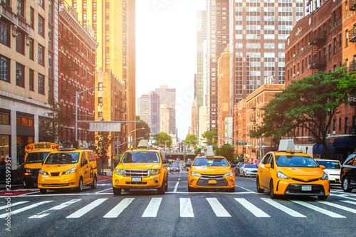 New York TAXI Yellow cabs waiting for green light on the crossroad of streets of New York City during sunny summer daytime
