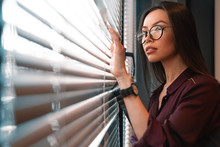 Asian Female In Eyeglasses Is Peeking Through The Window With Jalousie Of Her Work Cabinet With Black Watch On Her Hand