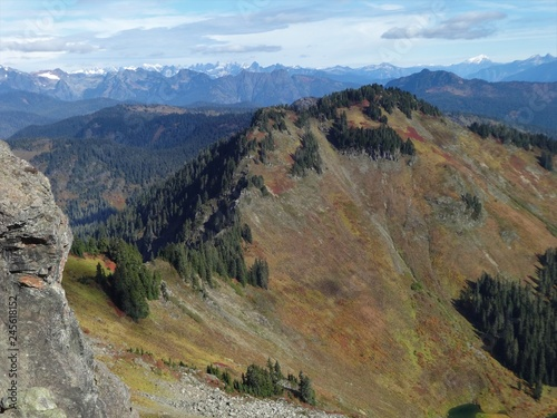Fotografía  Fall colors cover the slope of a mountain with the rugged peaks of the North Cas